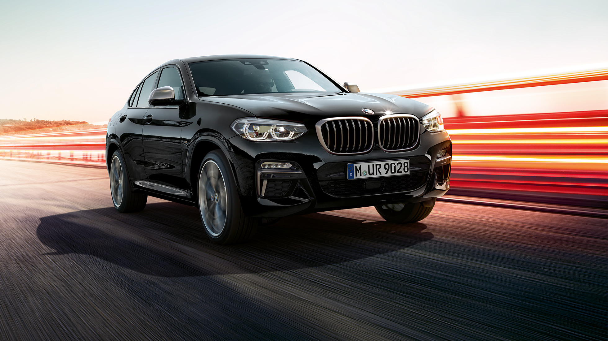 BMW X4 M40i in Black Sapphire metallic, exterior, three-quarter front view, left side with light strips.
